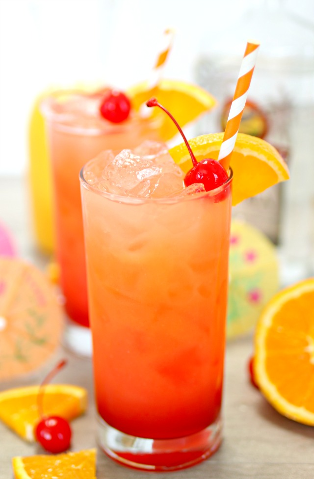 tequila sunrise cocktail with orange wedge and cherry